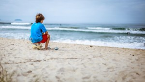 child sitting on a soccer ball at the beach