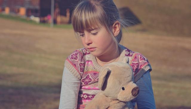girl with teddy bear looking sad