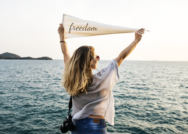 woman by the sea holding a sign saying freedom