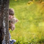 Girl with teddy bear peeking around a tree
